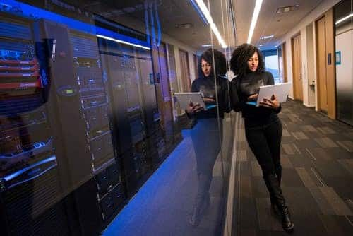 Woman Holding Laptop Beside Glass Wall